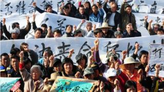 Villagers hold banners and placards during a protest rally by residents of Wukan, a fishing village in the southern province of Guangdong, as they demand the government take action over illegal land grabs and the death in custody of a local leader on 19 December 2011.