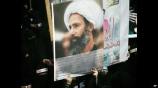 Shia women protesters hold a poster of Sheikh Nimr Baqir al-Nimr at the funeral of three people killed at a demonstration following his arrest (30 September 2012)