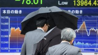 People walk past a share prices board in Tokyo