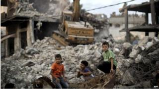 Children sit amid rubble in Shejaiya, Gaza (12/10/14)