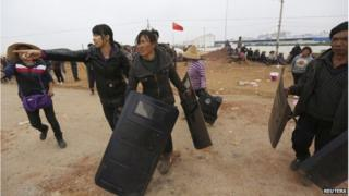 Villagers carry police shields taken from police injured during clashes at Fuyou village in Jinning county, Kunming, Yunnan province, 15 October 2014