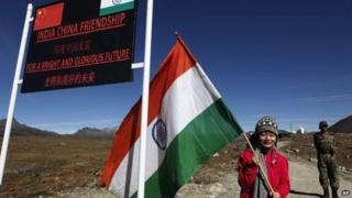 An Indian girl poses for photos with an Indian flag at the Indo China border in Bumla at an altitude of 15,700 feet (4,700 meters) above sea level in Arunachal Pradesh, India.