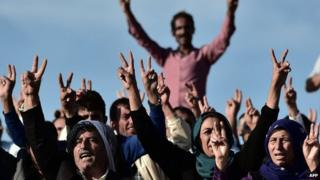 Kurdish people shout slogans while standing upon a hill opposite the Syrian town of Kobane, also known as Ain al-Arab, in the south-eastern village of Mursitpinar, Sanliurfa province, 15 October 2014