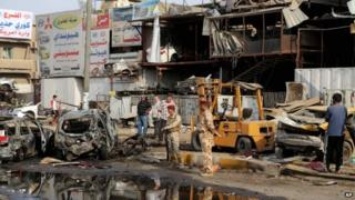 Security forces inspect the site of a car bomb explosion in Talibiya in Baghdad, Iraq on 16 October 2014