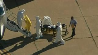 A man with a clipboard watches Ebola patient Amber Vinson being loaded onto a plane.