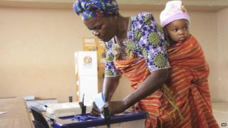 A woman with a child on her back casts her vote at a polling station in Maputo. Photo: 15 October 2014