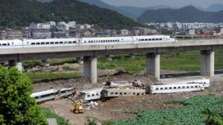A high-speed train runs past the accident site of the earlier collision of two trains on July 24, 2011 in Wenzhou, Zhejiang Province of China