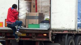 An illegal migrant steps into a truck