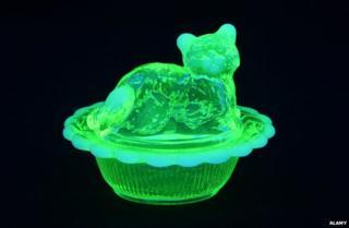 Uranium or vaseline glass cat in a basket shown under black light.