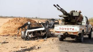 "Fighters of Libya""s Fajr Libya (Libyan Dawn) drive their pick up truck mounted with a machine gun near a burnt car, south of the town of Wershfana on October 13, 2014"