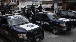 Members of the Mexican Federal Police are seen in a street of Teloloapan on 19 October, 2014.