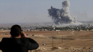 A man watches from a hill as smoke rises after an US-led coalition airstrike on Kobane, Syria, on the Turkish side of the border, near Suruc district, Sanliurfa, Turkey, 18 October 2014