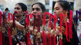 Pakistani women look at 'rakhi' (sacred thread) at a roadside shop ahead of the Hindu festival Raksha Bandhan in Karachi - August 2014