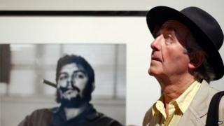 Swiss photographer Rene Burri poses in front of his most famous photo of Che Guevara in Lausanne, Switzerland on 24 June 2004