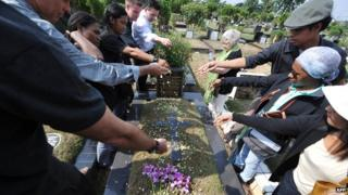 Indonesian journalists along with foreign colleagues sow flowers onto a tomb of five journalist as Australian Shirley Shackleton (C), widow of Australian journalist Greg Shackleton - killed in Balibo in what is now East Timor on 16 October 1975 - looks on at a cemetery in Jakarta on 14 October 2012