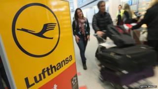 Passengers walking past Lufthansa sign
