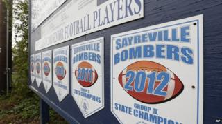 Championship banners for the town high school American football team hang from a wall in Sayreville, NJ