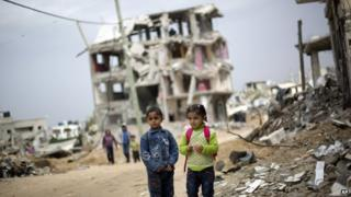 Palestinian school children walk through destroyed houses in Gaza City's Shejaiya neighbourhood. Photo: 19 October 2014