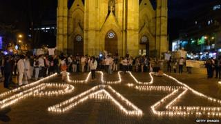 """Supporters of the peace process with the Farc form the word """"Peace"""" with candles on the floor during an event in Bogota on 11 June, 2014"""