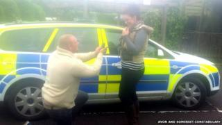 Caine Hutchings and Emily Dukeson in front of a police car