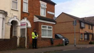 A police officer on guard outside a house