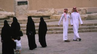 Riyadh family in traditional dress, Saudi Arabia. Men dressed in white and women in black dress