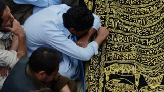 Pakistani Shiite Muslim mourners sit beside the coffin of a community member killed in an attack by gunmen on a passenger mini bus