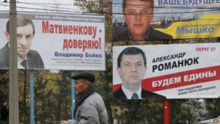 A man walks past election posters in Kiev, Ukraine on 23 October 2014