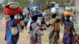 Displaced South Sudanese women carry their possessions