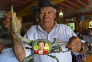 Restaurant owner Luiz da Gia with his famous pet crab displaying a Dilma Rousseff sticker