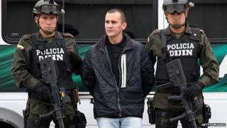 Colombian policemen guard the FARC member Alexander Herrera before his extradition to the United States in Bogota on 9 March 2012.