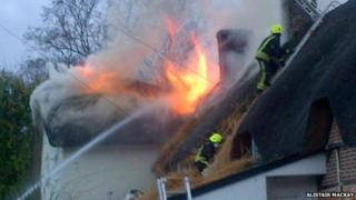 Thatched cottages on fire