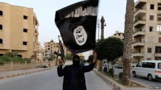 Islamic State militant waves flag in Raqqa, Iraq, on 29 June 2014