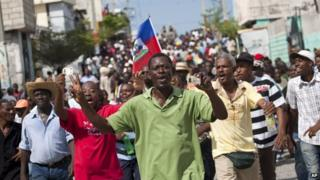 Demonstrators march during an anti-government protest in Port-au-Prince on 26 October 2014.