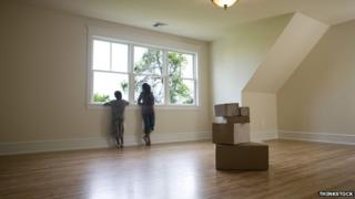 Two children stare out of a window in an empty room with boxes