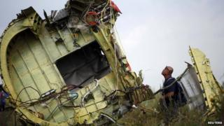 A Malaysian air crash investigator inspects the crash site of Malaysia Airlines Flight MH17, near the village of Hrabove (Grabove), Donetsk, Ukraine on 22 July 2014