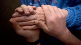 Carer holds the hand of an elderly patient