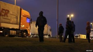 Migrants standing by lorries at ferry port in Calais