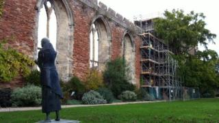 Scaffolding around the stone arch window being repaired