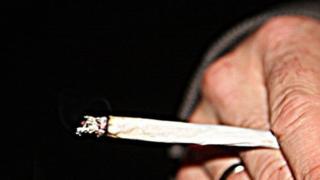 A man holding a cannabis cigarette