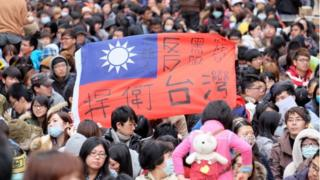 Protesters displays a Taiwan flag with the words 'protect Taiwan' on it during ongoing protests by thousands of people outside the parliament in Taipei on March 22, 2014. Student protesters occupying Taiwan's legislature to stop the government from ratifying a contentious trade pact with China on March 21