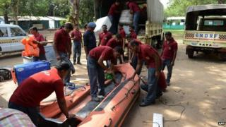 Indian rescue workers from the 6 Battalion of National Disaster Response Force (NDRF) check an inflatable boat at their headquarters at Chiloda near Gandhinagar, some 30 kms from Ahmedabad on October 28, 2014