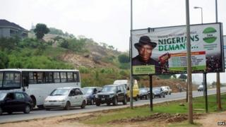 Cars pass an election poster of Nigerian President Goodluck Jonathan at a road in Abuja, Nigeria (27 October 2014)