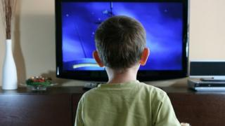 A boy stands in front of a television screen.
