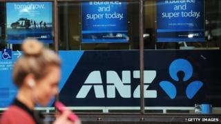 A woman walks past Australia and New Zealand Banking Group (ANZ) signage displayed