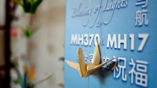 Origami paper cranes hang on a board offering prayers and condolences to the Malaysia Airlines MH370 and MH17 victims and their families at a Chinese bereavement centre in Kuala Lumpur on September 9