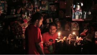 A Bangladeshi salesman interacts with a customer during a blackout in Dhaka - 1 November 2014