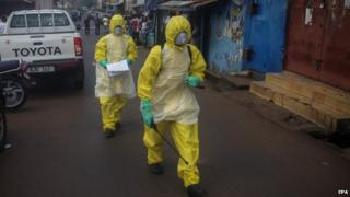 Sierra Leone health workers walk in central Freetown, Sierra Leone on 24 October 2014