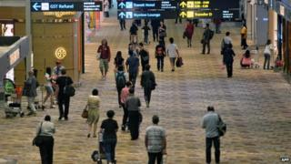 This general view shows passengers in the transit hall of Changi International Airport in Singapore on 8 May 2014