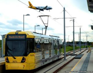 plane flies over tram at Manchester airport stop